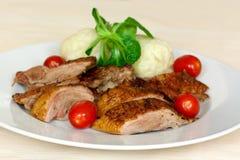 Gebackene Ente-Scheiben mit Mehlklößen, Kirschtomaten, G Stockfotos