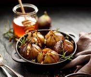 Gebackene Feigen angefüllt mit Gorgonzola-Käse, Kiefernnüssen, Honig und Kräutern in einem schwarzen Teller auf einem dunklen, St lizenzfreies stockfoto