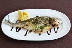 Gebackene Fische mit Soße und Zitrone Stockbild