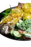 Gebackene Forelle auf einer Platte mit einem Salat von Arugula, von Tomaten, von Gurken und von jungen Kartoffeln mit dem Dill lo stockbild
