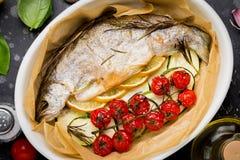 Gebackene ganze weiße Forellenfische in der keramischen Backform mit zucchin stockfoto