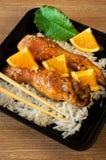 Gebackene Hühnerbeine mit Reis und Orange Stockbilder