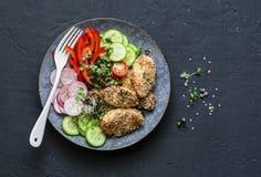 Gebackene Hühnerbrust des indischen Sesams Kruste und Frischgemüse Gebackenes Huhn und Tomaten, Gurken, Pfeffer, Rettiche, Mikro  lizenzfreie stockbilder