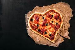 Gebackene Herz-förmige selbst gemachte Pizza auf einem Schneidebrett auf dunklem hölzernem Hintergrund Abschluss oben Lizenzfreies Stockbild
