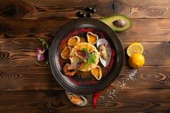 Gebackene Kalmarringe mit Reis und Gew?rzen im Schwarzblech stockfotos