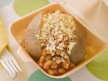 Gebackene Kartoffel mit gebackenen Bohnen und Käse in einem Nehmen Stockbilder