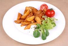 Gebackene Kartoffelkeile mit tzatziki und Salat Lizenzfreie Stockfotos