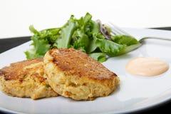Gebackene Krabbenküchlein auf Platte mit Salat Stockfotos