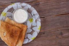 Gebackene Pfannkuchen auf einer Platte mit Sauerrahm Stockbild