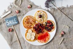 Gebackene Pfannkuchen oder selbst gemachte Kuchen Auf die Oberseite wird mit Beeren, Früchten, Honig und Stau auf rustikalem Hint stockfotos
