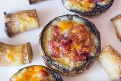 Gebackene Pilzkappen angefüllt mit Salami, Prosciutto, Knoblauch, Butter und Kräutern stockbilder