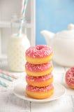 Gebackene Schaumgummiringe mit rosa Glasur und besprüht Stockfoto