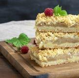 Gebackene Scheiben der Torte mit Äpfeln auf einem braunen hölzernen Brett lizenzfreies stockfoto