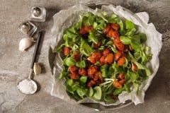 Gebackene Tomaten mit Knoblauchsalz und -salat stockfoto