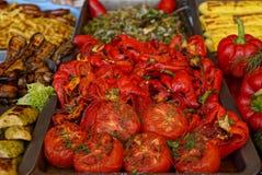 Gebackene Tomaten und Pfeffer auf Behältern stehen auf dem Tisch mit anderen Tellern Stockbilder