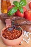 Gebackene weiße Bohnen mit Tomaten und Basilikum Stockfotografie