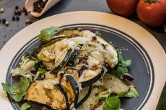 Gebackene Zucchini und Aubergine auf dem Eissalat besprüht mit Käse Stockfotografie