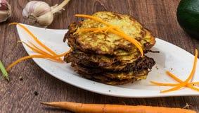 Gebackene Zucchini und Aubergine auf dem Eissalat besprüht mit Käse Stockfoto