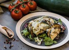 Gebackene Zucchini und Aubergine auf dem Eissalat besprüht mit Käse Lizenzfreies Stockbild