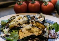 Gebackene Zucchini und Aubergine auf dem Eissalat besprüht mit Käse Stockbilder