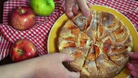 Gebackener Apfelkuchen Weibliche und männliche Hände, die Scheiben des Apfelkuchens von der Platte herausnehmen stock video footage