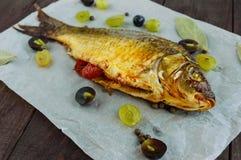 Gebackener Fischkarpfen, angefüllter grüner Pfeffer und Trauben stockfotos