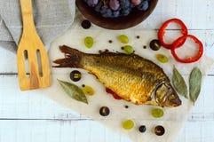 Gebackener Fischkarpfen, angefüllter grüner Pfeffer und Trauben stockfotografie