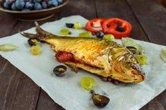 Gebackener Fischkarpfen, angefüllter grüner Pfeffer und Trauben stockbilder