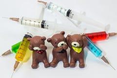 Gebackener Lehmteddybär mit den Plastikspritzen, die Mehrfarbenlösungen enthalten Lizenzfreies Stockfoto