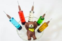 Gebackener Lehmteddybär mit den Plastikspritzen, die Mehrfarbenlösungen enthalten Lizenzfreies Stockbild