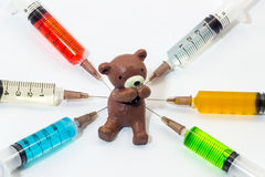 Gebackener Lehmteddybär mit den Plastikspritzen, die Mehrfarbenlösungen enthalten Stockfoto