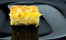 Gebackener Reispuddingnachtisch versüßt mit Zuckerpulver auf schwarzem Teller für Lebensmittelkonzept Lizenzfreie Stockbilder