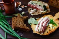 Gebackener Schinken mit Brot und Gewürzen auf einer dunklen Tabelle Stockfoto