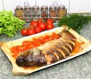 Gebackener silberner Karpfen mit Tomate und Zitrone Stockfotos