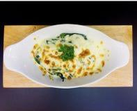 Gebackener Spinat mit Käse in der weißen Schüssel stockbilder