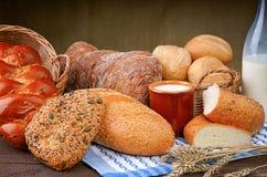 Gebackenes Brot mit Milchschale und -flasche auf der Tischdecke Stockfotografie