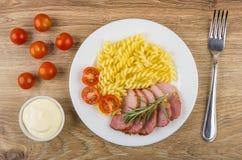 Gebackenes carbonade mit Tomaten und Teigwaren in der Platte, Majonäse Lizenzfreies Stockfoto