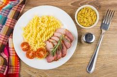 Gebackenes carbonade mit Tomaten und Teigwaren in der Platte, Senf, peppe Lizenzfreie Stockbilder