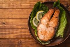 Gebackenes Forellensteak in den Tonwaren mit Salat und Scheiben der Zitrone Lizenzfreie Stockfotos