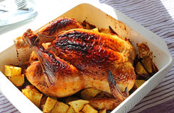 Gebackenes Huhn mit Kartoffeln in der weißen keramischen Schüssel Stockfoto