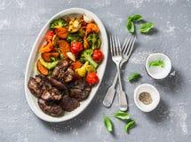 Gebackenes Saisongemüse - Süßkartoffeln, Brokkolikohl, Gemüsepaprikas, Kirschtomaten, rote Rüben, Knoblauch, Zucchini und Huhn stockbild