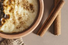 Gebackenes türkisches sutlac Nachtisch des Reispuddings in der Töpferwarenkasserolle mit Zimtstangen lizenzfreies stockbild