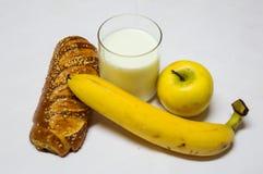 Gebakje, Banaan, Aplle en Glas Melk Stock Foto's