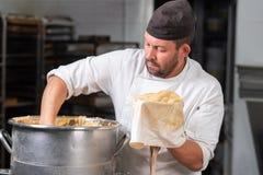 Gebakje die cheff de gebakjezak vullen met slagroom bij de keuken van de patisserie royalty-vrije stock foto's