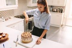 Gebakjechef-kok die een cake snijden royalty-vrije stock fotografie