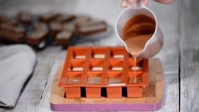 Gebakjechef-kok die een siliconevorm vullen met een chocolademousse Het maken van Frans dessert stock video