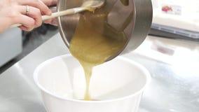 Gebakjechef-kok die hete room van een pan gieten in een kom royalty-vrije stock afbeeldingen