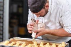 Gebakjechef-kok die met banketbakkerijzak room drukken bij patisserie stock afbeelding