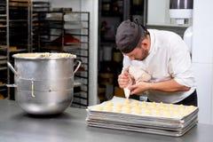 Gebakjechef-kok die met banketbakkerijzak room drukken bij patisserie stock afbeeldingen