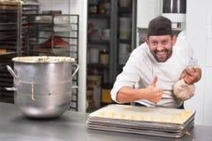 Gebakjechef-kok die met banketbakkerijzak room drukken bij patisserie stock foto